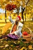 Маленькая девочка бросает букет листьев осени стоковые изображения rf