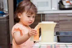 Маленькая девочка варя еду в кухне стоковые фотографии rf
