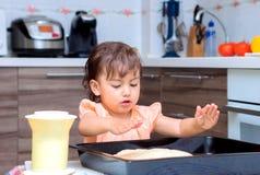 Маленькая девочка варя еду в кухне стоковое изображение
