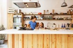 Маленькая девочка варя с ее матерью в кухне стоковые изображения