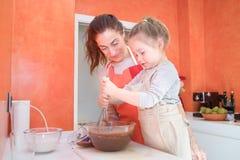Маленькая девочка взбивая сливк шоколада с наблюдать матери Стоковые Фотографии RF