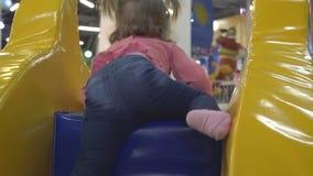 Маленькая девочка взбирается вверх на пестротканом раздувном холме, играх в игровой детей видеоматериал
