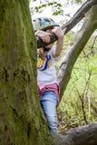Маленькая девочка взбираясь на дереве Стоковое Фото