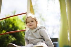 Маленькая девочка взобралась на дети сползает на спортивную площадку для детей и очень счастлива сыграть стоковые изображения rf
