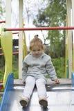 Маленькая девочка взобралась на дети сползает на спортивную площадку для детей и очень счастлива сыграть стоковая фотография