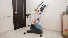 Маленькая девочка включенная на велотренажере в комнате видеоматериал