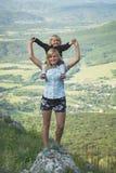 Маленькая девочка владением матери на ее плечах Стоковые Изображения