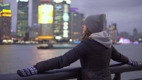 Маленькая девочка во взглядах черной куртки и шляпы на видимостях Шанхая на портовом районе Vaitan видеоматериал