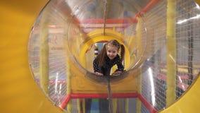 Маленькая девочка вползая через тоннель на земле игры детей внутри помещения сток-видео