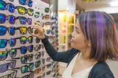 Маленькая девочка выбирает новые стекла в магазине optician стоковое фото rf