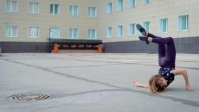 Маленькая девочка выполняет современный танец на улице города в дневном времени в лете, завихряясь и закручивая акции видеоматериалы