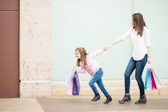 Маленькая девочка вытягивая ее shopaholic мать вне с магазина Стоковые Изображения RF