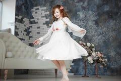 Маленькая девочка в белом платье dansing стоковые изображения rf