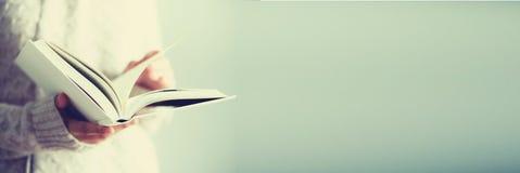Маленькая девочка в белым книге кардигана раскрытой чтением скопируйте космос образ жизни и концепция школы знамена стоковые фотографии rf