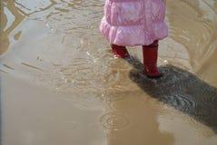 Маленькая девочка в ботинках идя на большую лужицу Стоковая Фотография