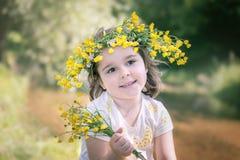 маленькая девочка в венке желтых цветков стоковое фото