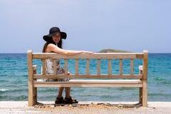 Маленькая девочка в голубой шляпе сидя на деревянной скамье на береге Средиземного моря на острове Крита Стоковая Фотография