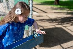 Маленькая девочка в голубом платье используя выпивая фонтан стоковое фото