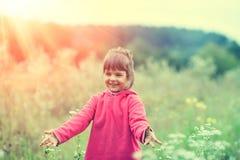 Маленькая девочка в идти в поле цветков стоковое фото