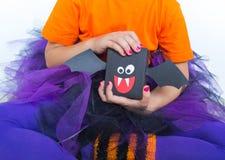 Маленькая девочка в костюме ведьмы держит летучую мышь стоковое фото