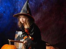 Маленькая девочка в костюме ведьмы на венике готовом для того чтобы лететь Стоковое Фото