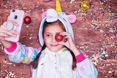 Маленькая девочка в костюме единорога Принципиальная схема рождества Девушка лежа на деревянной предпосылке, много красочном conf стоковое фото rf