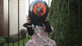 Маленькая девочка в костюме принцессы держа черный воздушный шар Она смотрит очень счастливой потому что сегодня праздник хеллоуи видеоматериал