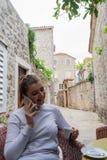 Маленькая девочка в кофе белой длинной рубашки выпивая в террасе и звонить в ее умном телефоне Женщина держа чашку в a стоковое изображение rf