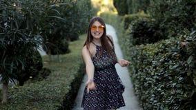 Маленькая девочка в красивом зеленом парке представляет для камеры и после этого весело бежит  акции видеоматериалы
