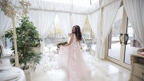 Маленькая девочка в красивом розовом платье в большой и светлой комнате, там много свечи и чувствительное оформление A видеоматериал