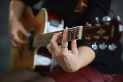 Маленькая девочка в красной кожаной мини-юбке и черном колготки играя гитару, конец-вверх, малую глубину поля стоковые фотографии rf