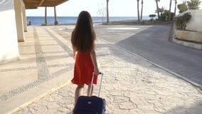 Маленькая девочка в красном платье путешествуя на улице с чемоданом сток-видео