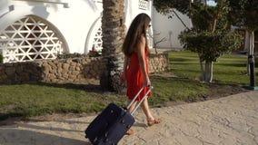 Маленькая девочка в красном платье путешествуя на улице с чемоданом видеоматериал