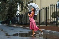 Маленькая девочка в красном платье с прозрачными танцами зонтика в дожде стоя в лужице стоковая фотография