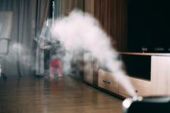 Маленькая девочка в красных брюках смотрит и касается увлажнитель Влага в концепции дома стоковая фотография rf