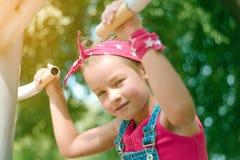 Маленькая девочка в красных тягах bandana вверх на имитаторе стоковые изображения rf