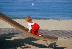 Маленькая девочка в красных overralls взбираясь вверх скольжение Стоковые Изображения RF