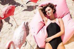 Маленькая девочка в купальнике лежа и загорая на большой розовой подушке рядом с фламинго на пляже красивейший портрет девушки Стоковые Изображения RF