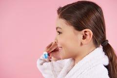 Маленькая девочка в купальном халате чистит зубы щеткой стоковая фотография rf