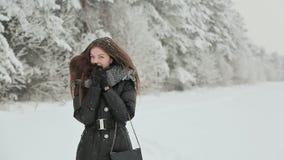 Маленькая девочка в одеждах зимы с длинными волосами наслаждается прогулкой вдоль покрытого снег леса под падая снегом акции видеоматериалы