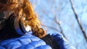 Маленькая девочка в парке слушая к музыке в наушниках Женщина идет через парк весны и наслаждается музыкой сток-видео