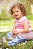 Маленькая девочка в платье лета сидя в поле стоковые фотографии rf