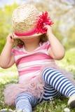Маленькая девочка в платье лета сидя в поле стоковые изображения
