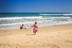 Маленькая девочка в пятнистых бегах для того чтобы развевать мальчик прибоя играет на пляже Стоковое фото RF