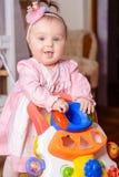 Маленькая девочка в розовом платье играет автомобиль игрушки около шпаргалки стоковые фото