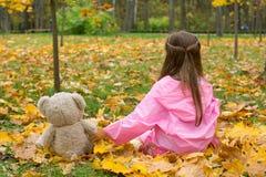 Маленькая девочка в розовом плаще держит плюшевый медвежонка за ее лапкой в осени стоковая фотография
