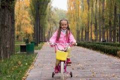 Маленькая девочка в розовом плаще и резиновые ботинки едет bi стоковые изображения rf