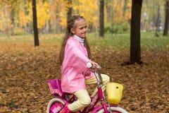 Маленькая девочка в розовом плаще и в резиновых ботинках едет b стоковое изображение rf