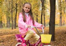 Маленькая девочка в розовом плаще стоит с велосипедом в стоковые изображения