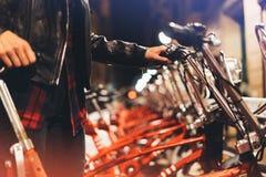 Маленькая девочка в черной кожаной куртке используя велосипед на свете bokeh зарева освещенности фона в городе ночи атмосферическ Стоковая Фотография